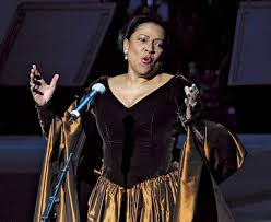 Soprano Kathleen Battle often tilted her head to one side when singing into her higher voice, as seen from this picture. Tilting the head in this manner unbalances the larynx, but many singers believe that they must make some physical change for rising pitch.
